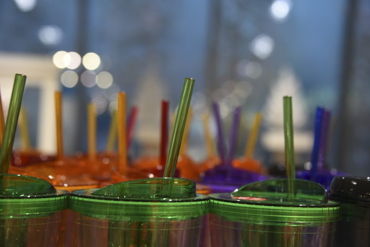 plastic pollution is manifest in the form of a plastic cup, with a plastic straw.